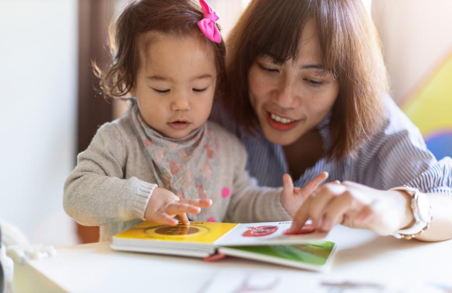 Mom reading to toddler girl